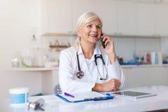 Vrouwelijke arts die mobiele telefoon in haar bureau met behulp van stock afbeeldingen