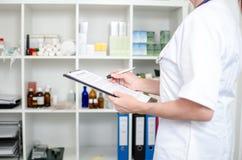 Vrouwelijke arts die nota's neemt stock afbeelding