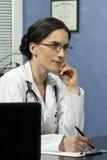 Vrouwelijke arts die nota's nemen stock foto's