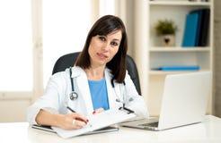 Vrouwelijke arts die omhoog voelend voorschrift en medische dossiers met klembord en laptop bureau werken stock afbeelding