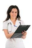 Vrouwelijke arts die op klembord schrijft, dat op wh wordt geïsoleerdo Stock Afbeelding