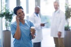 Vrouwelijke arts die op mobiele telefoon spreken Stock Fotografie