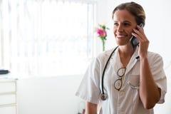 Vrouwelijke arts die op mobiele telefoon in verpleeghuis spreken Stock Foto