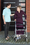 Vrouwelijke arts die oude vrouw met leurder bijstaan Stock Foto's