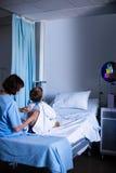 Vrouwelijke arts die patiënt met stethoscoop onderzoeken Stock Fotografie