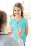 Vrouwelijke arts die pillen en water geven aan kind Royalty-vrije Stock Fotografie