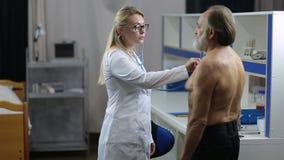 Vrouwelijke arts die stethoscoop met behulp van aan examenpatiënt stock videobeelden