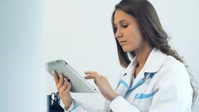 Vrouwelijke arts die tabletcomputer in medisch bureau met behulp van
