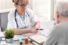 Vrouwelijke arts die voorschrift geven aan haar pati?nt stock fotografie