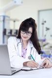 Vrouwelijke arts die voorschrift maken Stock Foto's