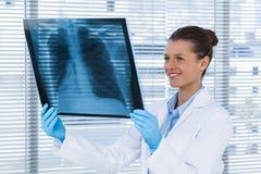Vrouwelijke arts die x-ray rapport onderzoeken Royalty-vrije Stock Foto