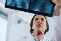 Vrouwelijke arts die x-ray rapport onderzoeken Stock Fotografie