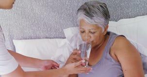 Vrouwelijke arts die zieke hogere vrouw een glas water op bed 4k geven stock videobeelden