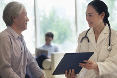 Vrouwelijke arts en geduldige zitting die beneden en medisch dossier in het ziekenhuis bespreken Royalty-vrije Stock Afbeeldingen