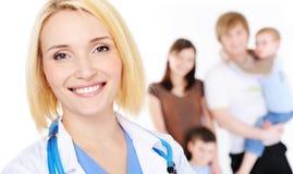 Vrouwelijke arts en jonge familie met twee kinderen stock foto's
