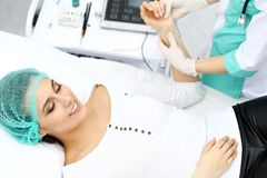 Vrouwelijke arts en jonge vrouwenpatiënt in het ziekenhuis De artsen onderzoeken meisjesimpuls die bij het bed, mening hierboven  stock afbeelding