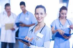 Vrouwelijke arts gebruikend tablet en glimlachend bij camera royalty-vrije stock fotografie