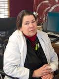 Vrouwelijke arts in haar bureau Stock Afbeeldingen