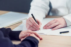 Vrouwelijke arts het schrijven nota's tijdens het geduldige medische examen van ` s Stock Foto's