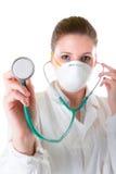 Vrouwelijke arts in masker met gerichte stethoscoop Stock Foto