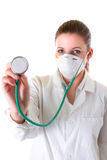 Vrouwelijke arts in masker met gerichte stethoscoop Stock Fotografie