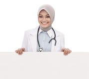 Vrouwelijke arts met de lege witte die raad van de stethoscoopholding op witte achtergrond wordt geïsoleerd Stock Foto