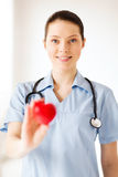 Vrouwelijke arts met hart Stock Foto