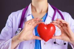 Vrouwelijke arts met het hart van de stethoscoopholding Stock Foto