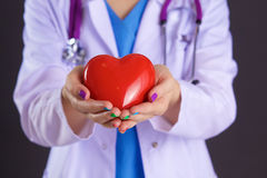 Vrouwelijke arts met het hart van de stethoscoopholding Royalty-vrije Stock Afbeeldingen