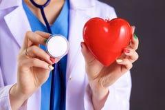 Vrouwelijke arts met het hart van de stethoscoopholding Royalty-vrije Stock Afbeelding