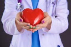 Vrouwelijke arts met het hart van de stethoscoopholding Stock Fotografie