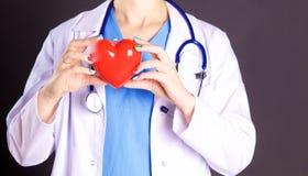 Vrouwelijke arts met het hart van de stethoscoopholding Stock Foto's