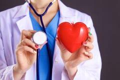 Vrouwelijke arts met het hart van de stethoscoopholding Stock Afbeelding