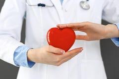 Vrouwelijke arts met het hart van de stethoscoopholding in haar wapens Gezondheidszorg en cardiologieconcept in geneeskunde stock afbeeldingen