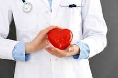 Vrouwelijke arts met het hart van de stethoscoopholding in haar wapens Gezondheidszorg en cardiologieconcept in geneeskunde stock fotografie