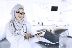 Vrouwelijke arts met klembord in de tandkliniek Stock Afbeeldingen