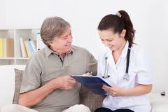 Vrouwelijke arts met patiënt thuis Royalty-vrije Stock Afbeeldingen