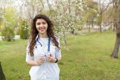 Vrouwelijke arts met stethoscoop in openlucht van het ziekenhuis in bloemtuin medische achtergrondexemplaarruimte royalty-vrije stock afbeelding