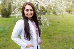 Vrouwelijke arts in openlucht van het ziekenhuis in bloemtuin medische achtergrondexemplaarruimte Vrolijke Jonge Vrouw stock foto's