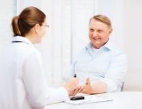 Vrouwelijke arts of verpleegster die de waarde van de bloedsuiker meten Stock Afbeeldingen
