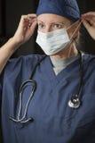 Vrouwelijke Arts of Verpleegster Putting op Beschermend Gezichtsmasker Royalty-vrije Stock Afbeeldingen