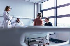 Vrouwelijke artsen bezoekende patiënt in het ziekenhuisruimte royalty-vrije stock fotografie