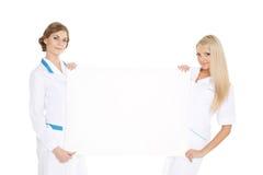 Vrouwelijke artsen met lege raad voor de tekst Stock Afbeeldingen