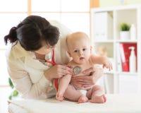 Vrouwelijke artsenpediater die babypatiënt controleren stock fotografie