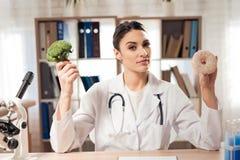 Vrouwelijke artsenzitting bij bureau in bureau met microscoop en stethoscoop De vrouw houdt broccoli en doughnut royalty-vrije stock afbeeldingen