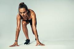 Vrouwelijke atleet in beginnende positie klaar voor de concurrentie stock afbeeldingen