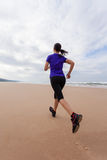 Vrouwelijke atleet die bij het strand op de Herfst lopen Stock Foto's
