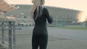Vrouwelijke atleet die bij stadion voor praktijk aankomen stock footage