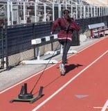 Vrouwelijke atleet die een slee met gewichten onderaan een spoor trekken stock foto