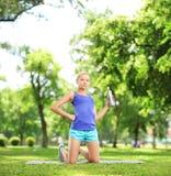 Vrouwelijke atleet die een waterfles houden en na excerici rusten Royalty-vrije Stock Fotografie